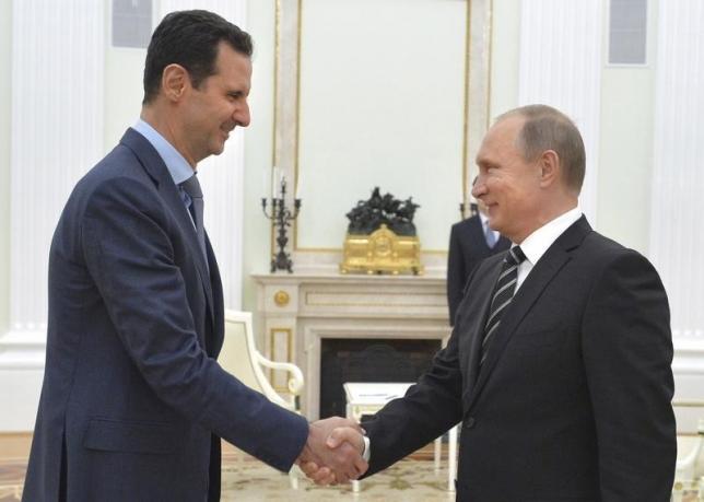 10月22日、ロシアのプーチン大統領(右)は、シリアのアサド大統領が、過激派組織「イスラム国」の掃討に向け、シリア国内の一部の反体制派武装組織との対話の可能性も視野に入れていることを明らかにした。モスクワで会談を行った両大統領、20日撮影。クレムリン提供(2015年 ロイター/Alexei Druzhinin)
